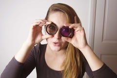 看通过镜头和微笑的年轻女人 摄影工具和设备 库存照片