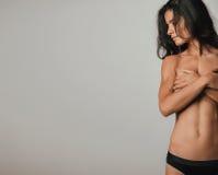 看部分地播种的裸体的妇女斜向一边 图库摄影