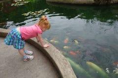 看金鱼池塘的逗人喜爱的矮小的红发女孩 免版税图库摄影