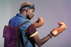 看金黄的拳击手套的年轻非裔美国人的人  免版税库存图片