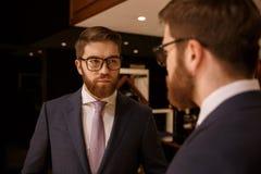 看镜子的严肃的年轻有胡子的商人 免版税库存图片