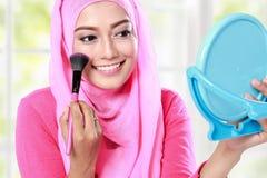 看镜子的快乐的少妇,当申请脸红时 免版税库存图片