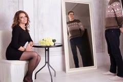 黑看镜子的礼服和人的小姐 免版税库存照片