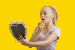 看镜子的美丽的少妇,当应用在黄色背景时的唇膏 免版税库存照片