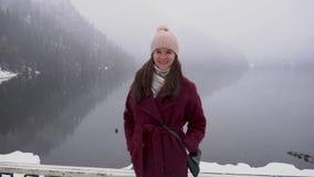 看阿布哈兹的Ritsa湖在冬天,转向和微笑照相机的妇女 股票录像