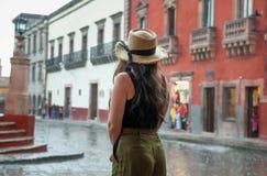 看雨风暴的帽子的少妇圣米格尔德阿连德镇中心  图库摄影