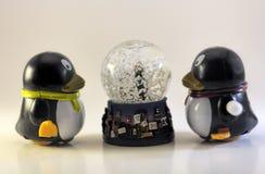 看雪地球的玩具企鹅 免版税库存照片