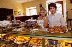 看面包店窗口不同的蛋糕的围巾的夫人 库存图片