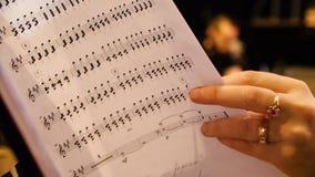 看音乐笔记的美丽的女性音乐作曲家 妇女看关于钢琴特写镜头的笔记 库存图片