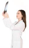 看顶头孤立的X-射线图片年轻女性医生 免版税库存照片
