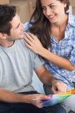 看颜色样品的愉快的夫妇装饰他们的房子 免版税库存图片