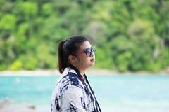 看风景视图的亚洲妇女佩带的太阳镜 海和gree 库存图片