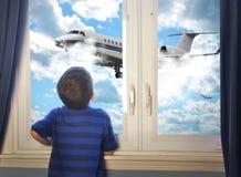 看飞行飞机的男孩在屋子里 免版税库存照片