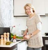 看食谱的微笑的妇女为烹调在互联网 库存图片