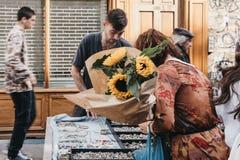 看首饰的妇女,拿着一束向日葵被购买在哥伦比亚路花市场上,伦敦,英国 库存图片