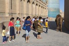 看骆驼的人们在市Khiva在乌兹别克斯坦 免版税图库摄影