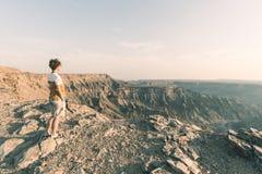 看鱼河峡谷,风景旅行目的地的一个人在南纳米比亚 在日落的膨胀的看法 旅行癖t 图库摄影