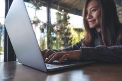 看,工作和键入在膝上型计算机键盘的一个美丽的亚裔女商人的特写镜头图象 免版税库存照片