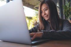 看,工作和键入在膝上型计算机键盘的一个美丽的亚裔女商人的特写镜头图象 库存照片