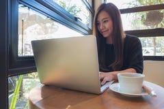 看,工作和键入在膝上型计算机键盘的一个美丽的亚裔女商人的特写镜头图象 免版税库存图片