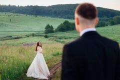 看从新郎的后面光芒四射的新娘 免版税图库摄影