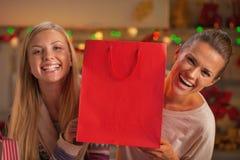看从购物袋的愉快的两个女朋友画象  免版税库存图片