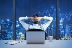 看从现代全景办公室的城市坐的商人的背面图  纽约晚上视图 免版税库存照片