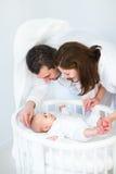 看他们的圆的小儿床的愉快的父母小儿子 库存照片