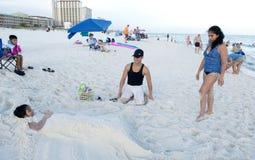 看他们的女儿的父母,在他们雕刻了她入在沙子后的一个美人鱼 库存照片