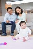 看他们的小女儿的愉快的父母 免版税库存图片
