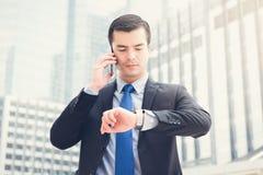 看他的手表的商人检查时间,当拜访时 免版税库存图片