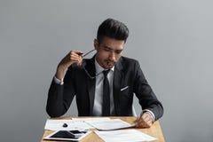 看他的文件的一个专业商人的画象,当坐在灰色背景时的办公桌 免版税库存照片