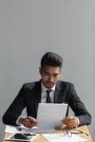看他的文件的一个专业商人的画象,当坐在灰色背景时的办公桌 免版税图库摄影