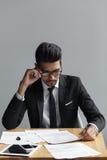 戴看他的文件的眼镜的成功的人,当坐在灰色背景时的办公桌 免版税库存照片