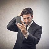 看他的智能手机的商人 免版税图库摄影
