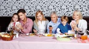 看他们的智能手机的家庭 图库摄影
