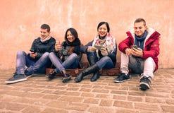 看他们的智能手机的小组年轻朋友在老镇 免版税库存照片