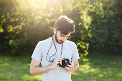 看他的照相机的年轻专业摄影师设法调整客观去做照片自然环境美化 英俊 图库摄影