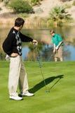看他的竞争者的男性高尔夫球运动员 免版税库存图片