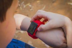 看他的红色巧妙的手表和接触它的逗人喜爱的年轻男孩 免版税图库摄影