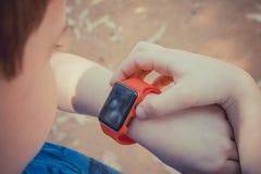 看他的红色巧妙的手表和接触它的逗人喜爱的年轻男孩 图库摄影