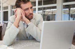 看他的膝上型计算机的皱眉的商人食用的桌咖啡 图库摄影
