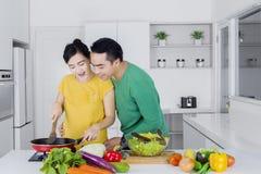 看他的妻子的人烹调在厨房里 免版税库存照片