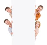 看从空白的广告牌的后面微笑的朋友 库存图片