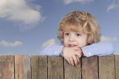看从篱芭上的小男孩, 库存图片