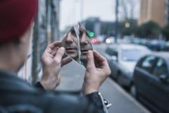 看他自己的低劣的人在一个被打碎的镜子 免版税图库摄影