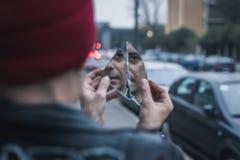 看他自己的低劣的人在一个被打碎的镜子 库存照片