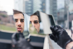 看他自己的美丽的年轻人在一个被打碎的镜子 免版税库存图片