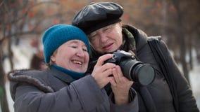 看他们自已照片照相机和微笑对冬日的两个前辈妇女,室外 免版税库存图片