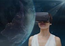 看3D行星的VR耳机的妇女反对与火光的天空背景 免版税库存图片